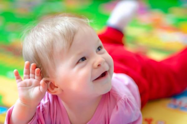 Sesja niemowlęca Łódź lifestyle dziewczynka na brzuchu leży i się usmiechay