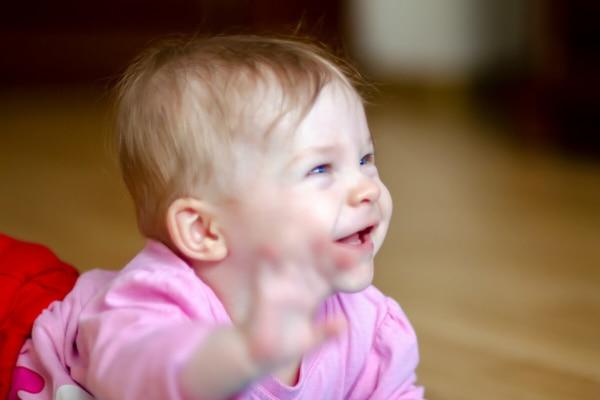 fotografia dziecięca sesja niemowlęca łódź dziewczynka na brzuchu cieszy się i macha ręką
