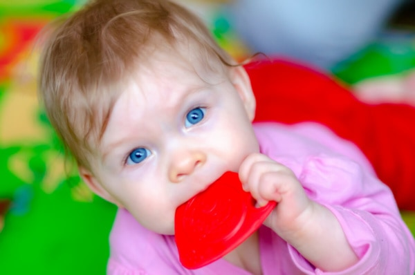 fotografia dziecięca sesja niemowlęca łódź dziewczynka na macie do zabawy z gryzakiem w ustach