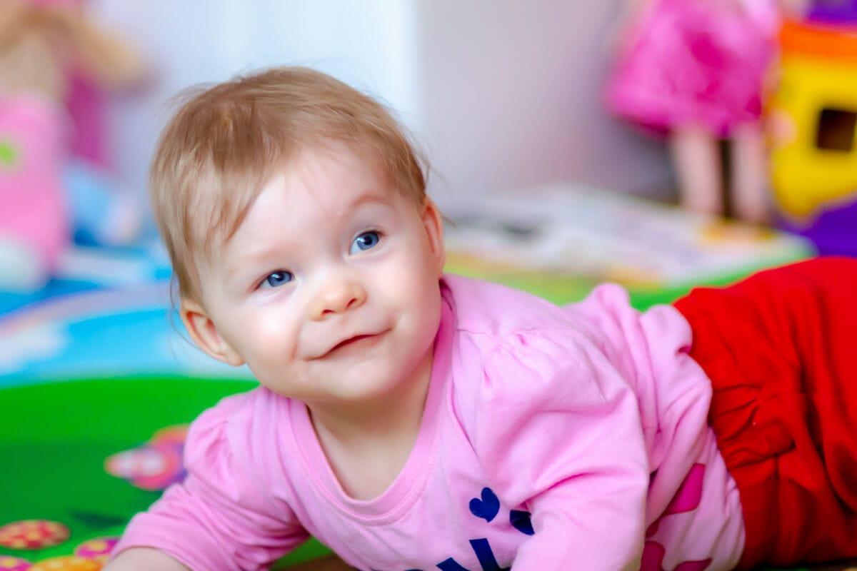 fotografia dziecięca sesja niemowlęca łódź dziecko na macie do zabawy uśmiecha się