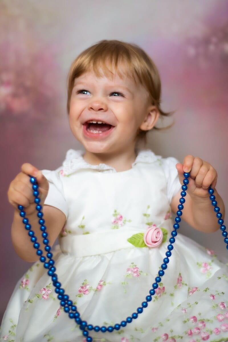 fotograf chrzest łódź sesja domowa studio mobilne uśmiechnięta dziewczynka z koralami w obu dłoniach Gbrysia 04