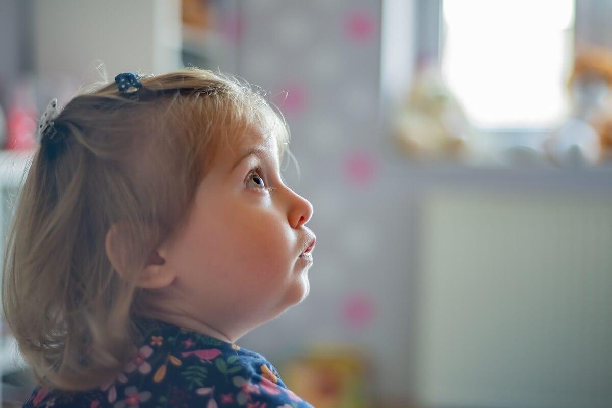 fotograf dziecięcy łódź sesja dziecięca domowa dziewczynka na tle okna wpatrzona w coś z boku