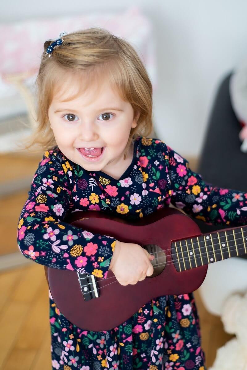 fotograf dziecięcy łódź sesja dziecięca domowa roześmiana dziewczynka grająca na gitarze