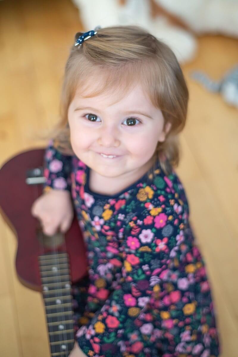 fotograf łódź sesja dziecięca domowa uśmiechnięta dziewczynka z gitarą patrząca do góry