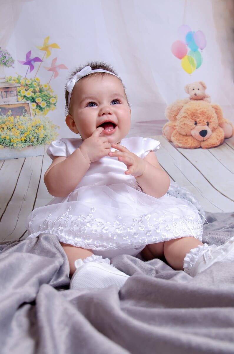fotograf chrzest łódź sesja domowa studio mobilne siedząca uśmiechnięta dziewczynka z palcem w buzi Ola 04