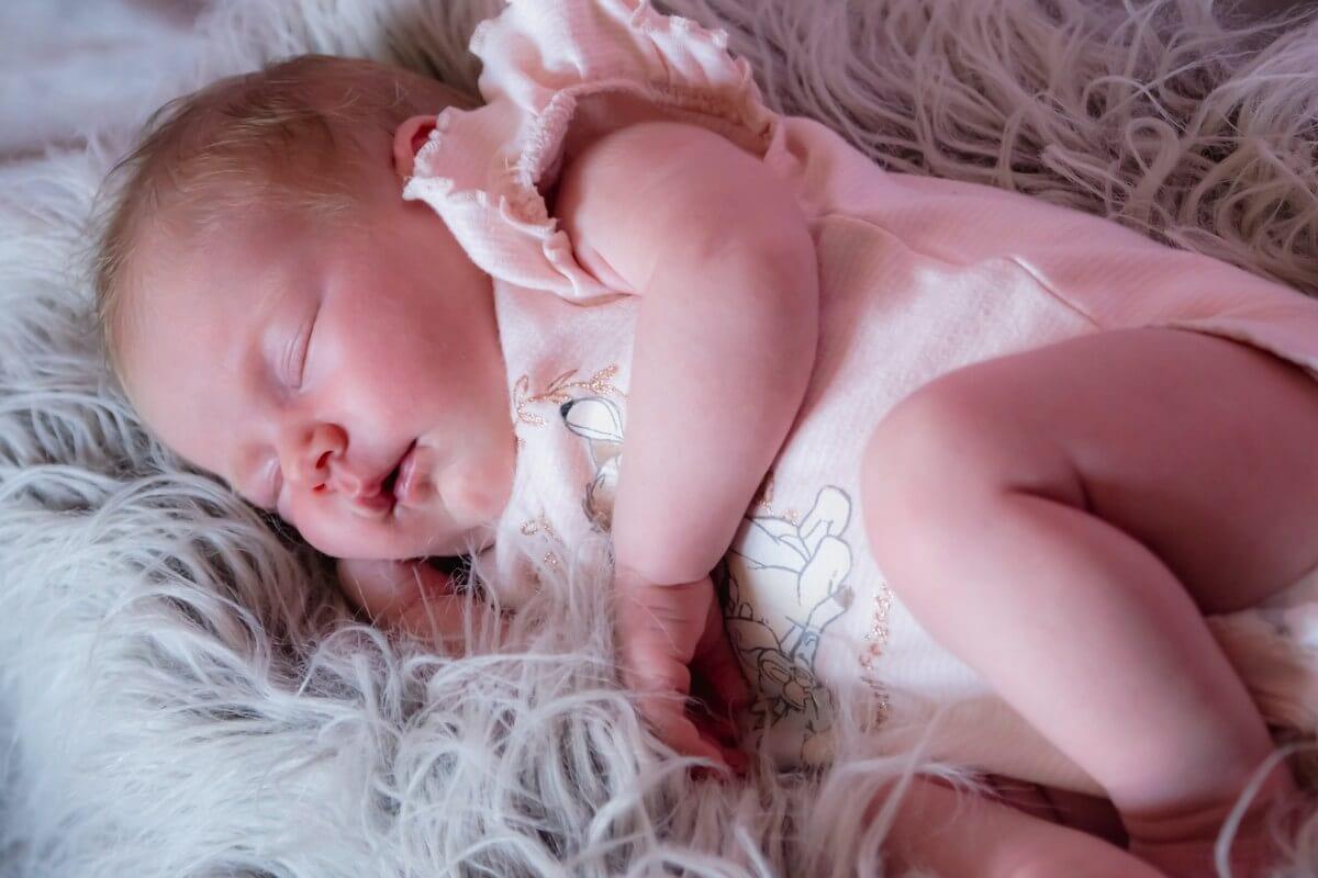 sesja noworodkowa łódź sesja domowa śpiący noworodek na boku na futerku