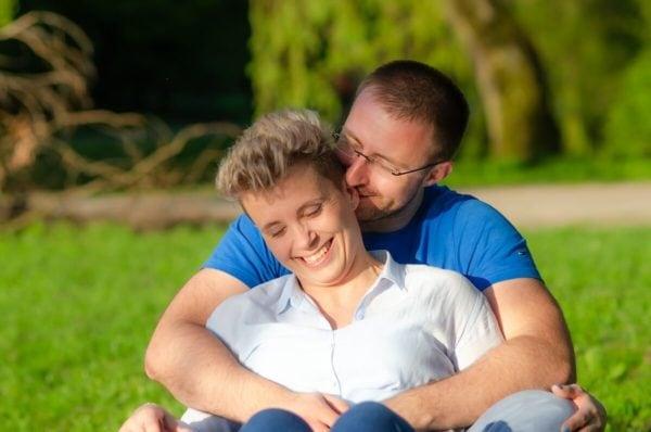 fotografia portretowa sesja pary zakochanych łódź para siedzi na trawie męczyzna coś szepcze do ucha