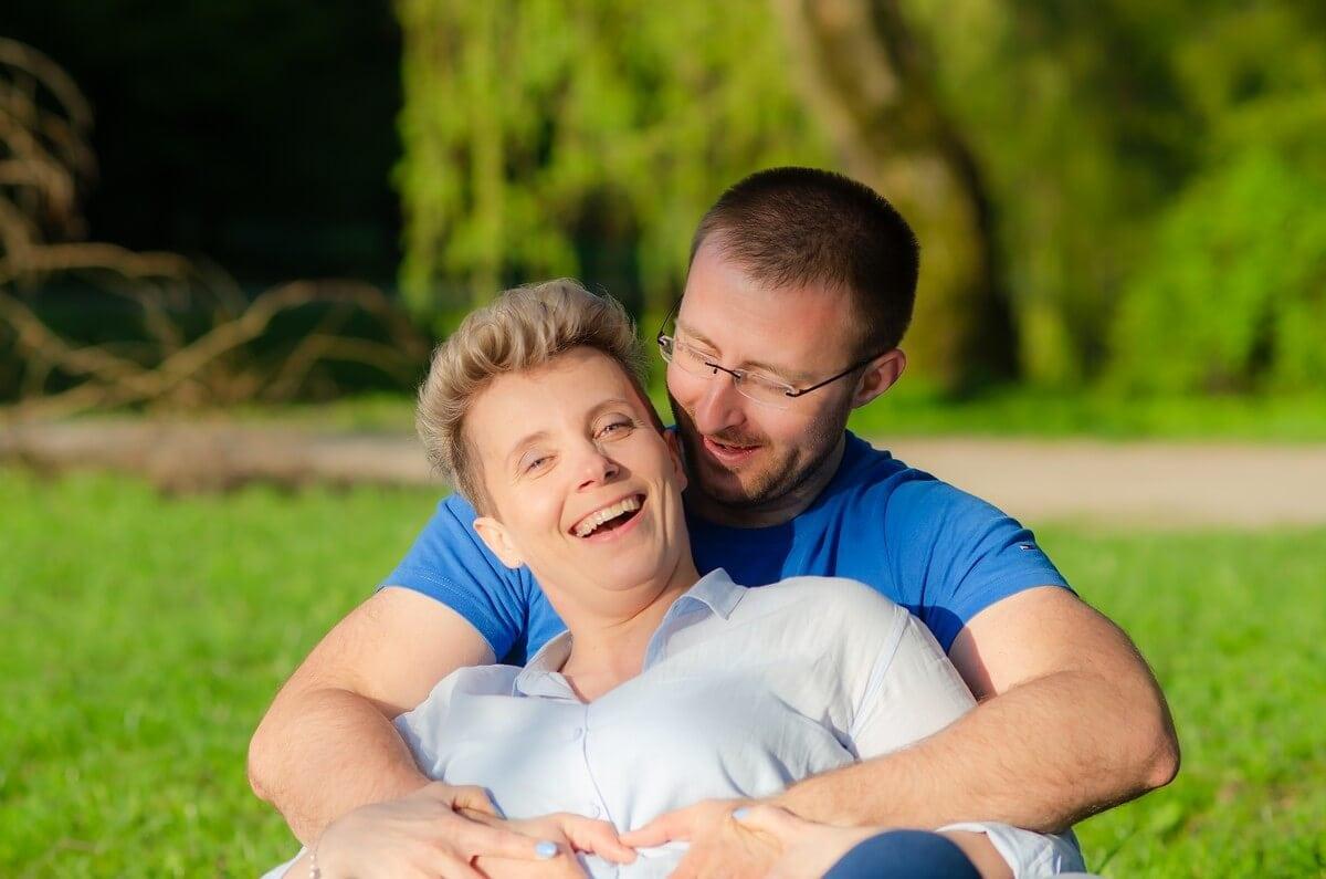 fotografia portretowa sesja pary zakochanych łódź zakochana para siedzi na trawie mężczyzna łaskocze swoją kobietę