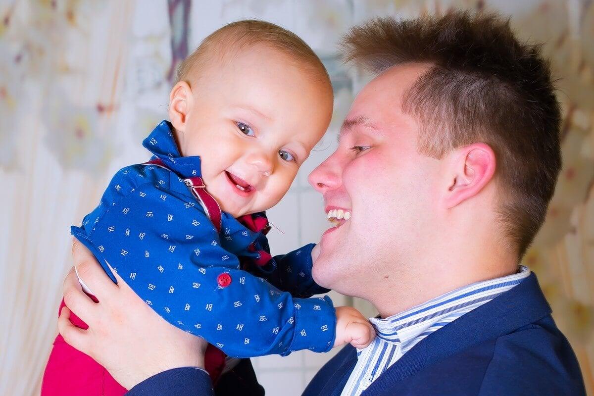 zdjęcia do chrztu Łódź sesja w domu tata z uśmiechniętym chłpcem