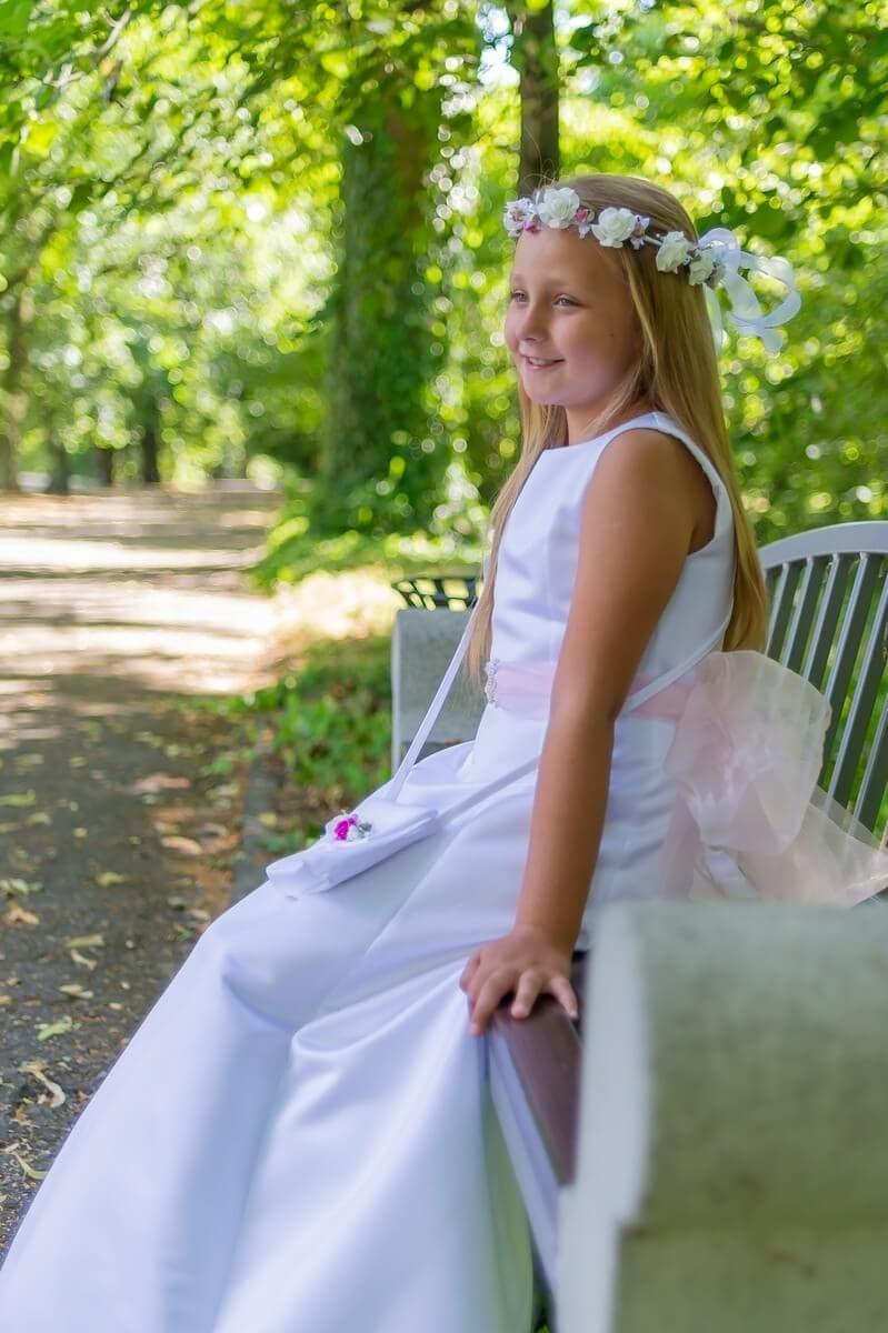 fotograf komunia łódź sesja komunijna plener dziewczynka na ławce w parku lekko się uśmiecha sara 01
