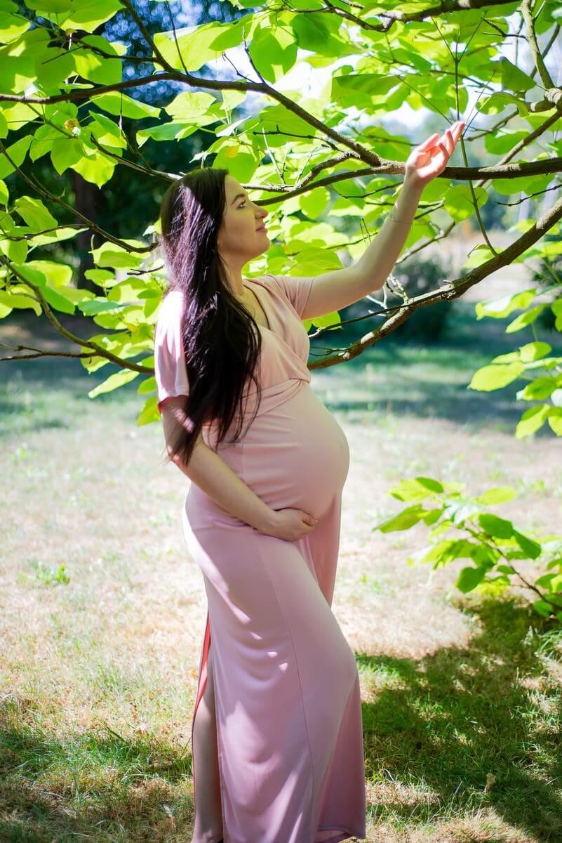 sesja ciążowa łódź plenerowa przyszła mama stoi na tle liści i przygląda im się Tomek i Sylwia 10