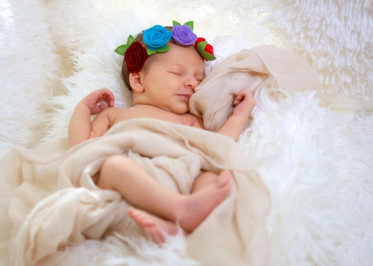 naturalna fotografia noworodkowa łódź sesja noworodkowa w domu dziewczynka śpiąca i uśmiechnięta z opaską w kwiatki A03