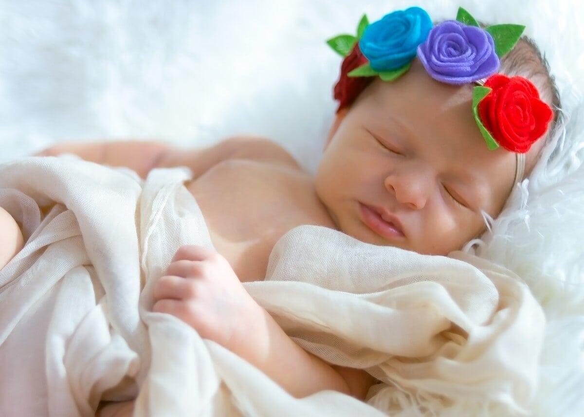 naturalna fotografia noworodkowa łódź sesja noworodkowa w domu dziewczynka śpiąca na białym futerku z opaską w kwiatki A02