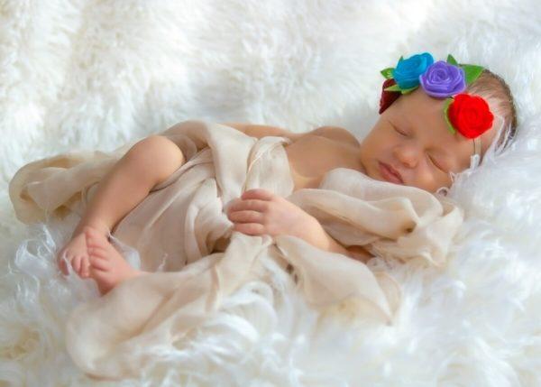 naturalna fotografia noworodkowa łódź sesja noworodkowa w domu dziewczynka śpiąca na białym futerku z opaską w kwiatki A01