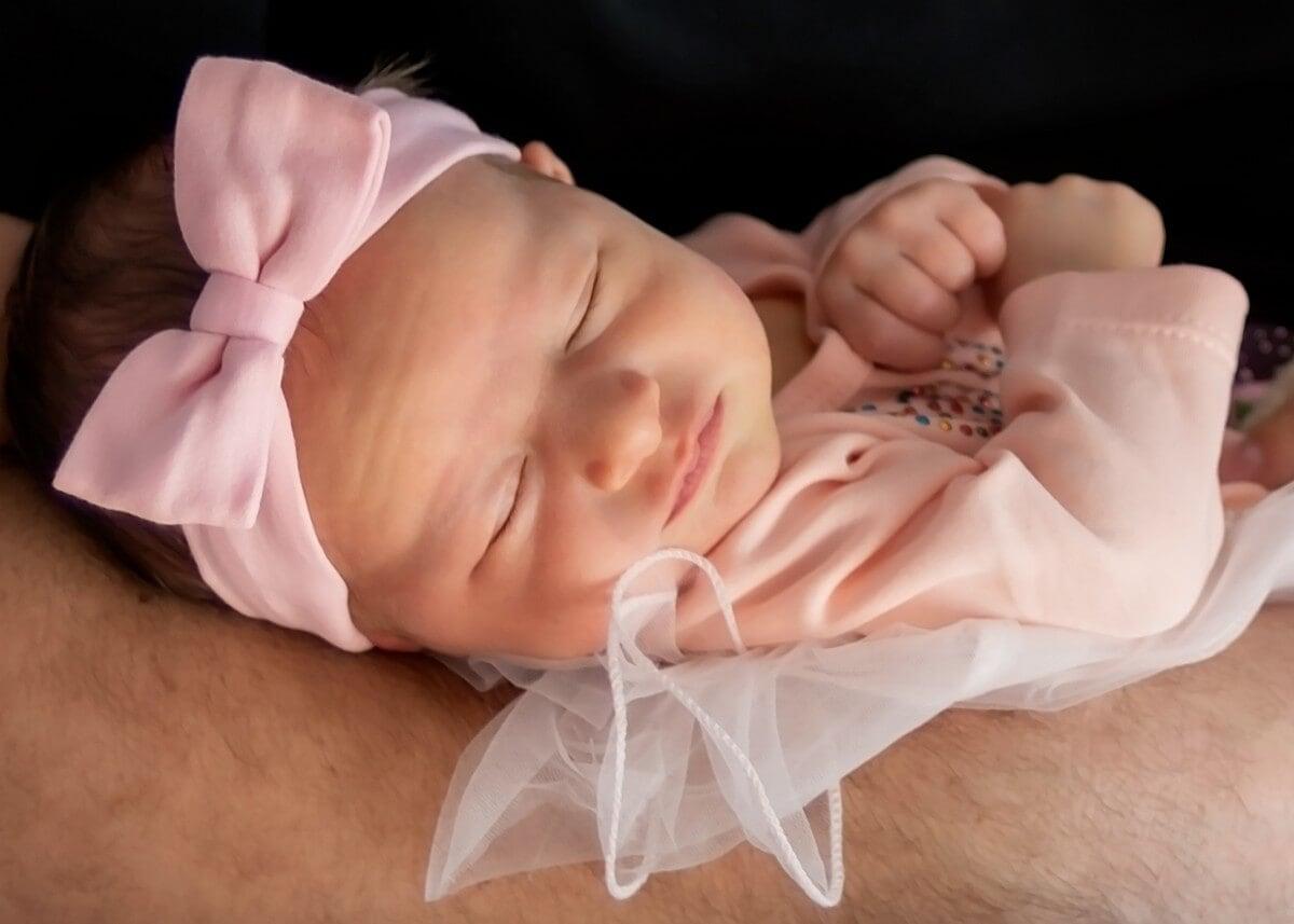naturalna fotografia noworodkowa łódź sesja noworodkowa w domu dziewczynka z kokardą śpiąca na ręku taty 0I1