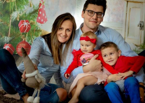 fotografia rodzinna łódź sesja świąteczna w domu rodzice z dwójką dzieci na tle choinki IA01