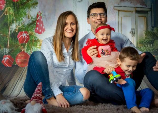 fotografia rodzinna łódź sesja rodzinna w domu sesja świąteczna rodzice z roześmianymi dziećmi na tle choinki IA04