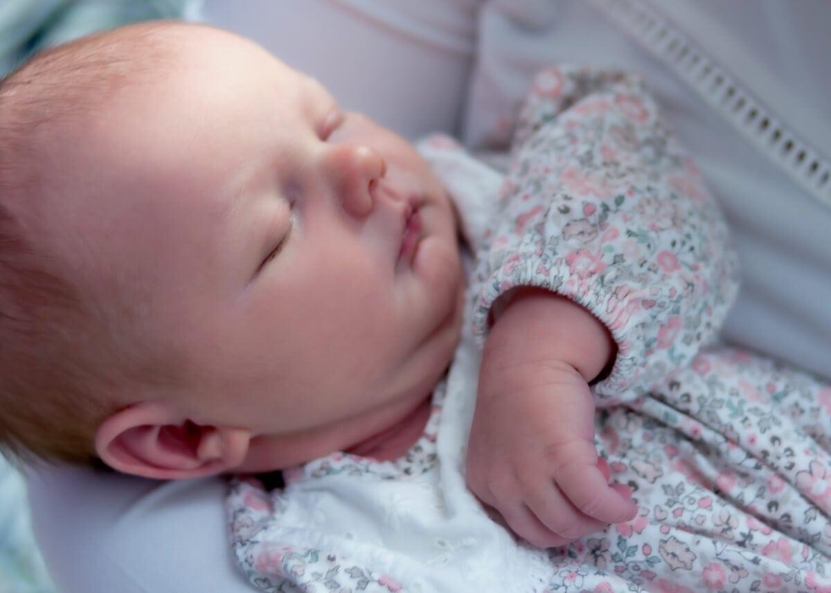 fotografia noworodkowa łódź sesja domowa łódź śpiący noworodek w sukience w kwiaty Laura 02