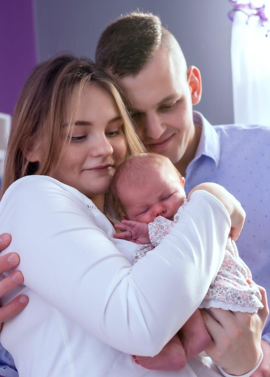 fotografia noworodkowa łódź sesja domowa łódź rodzice z noworodkiem na rękach Laura 03