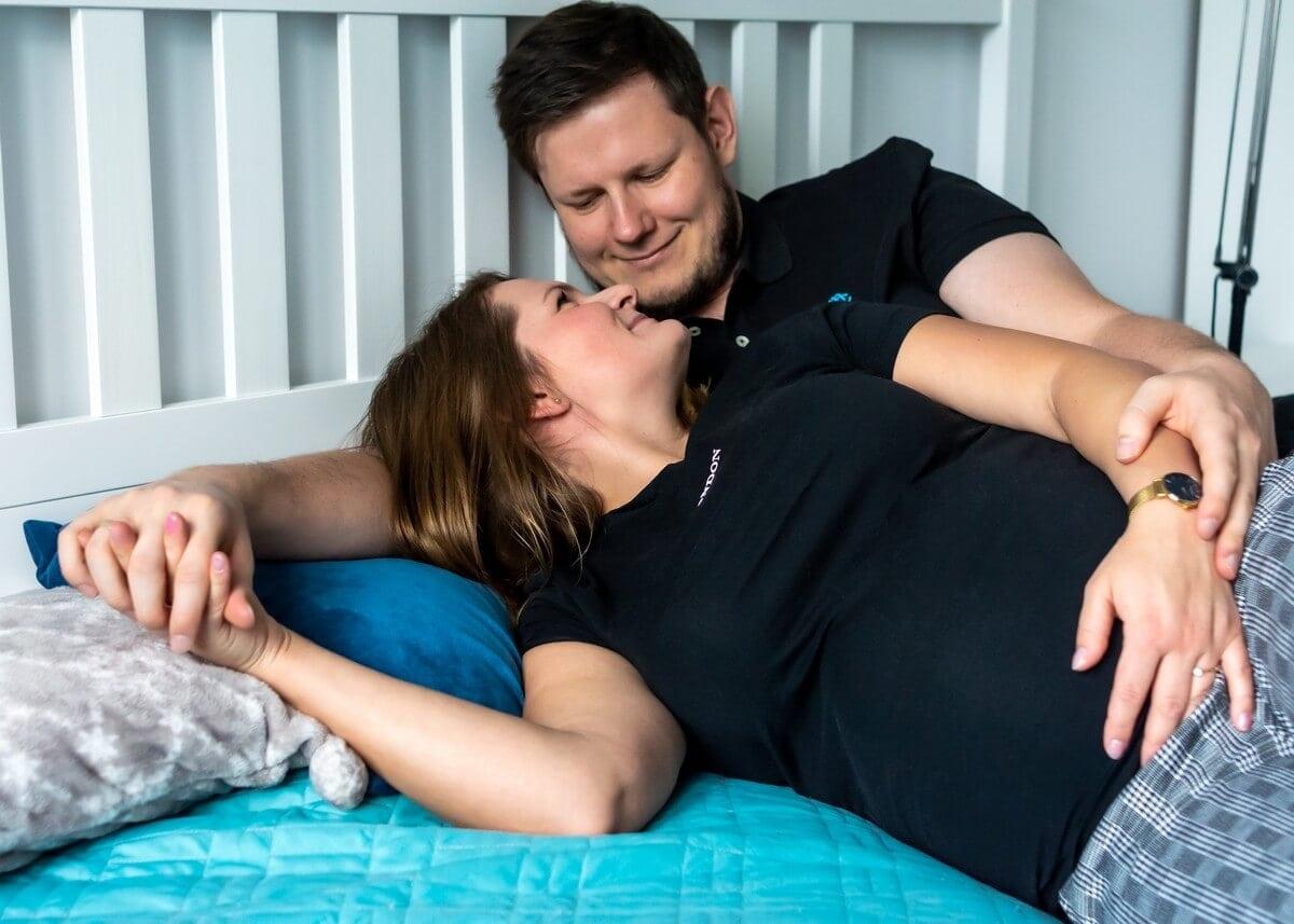 sesja ciążowa w domu łódź para leży na łóżku i patrzy na siebie RM 01