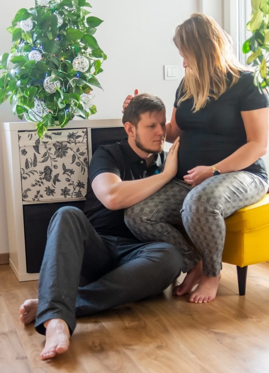 sesja ciążowa w domu łódź mężczyzna siedzi przy kobiecie i dotyka jej brzucha