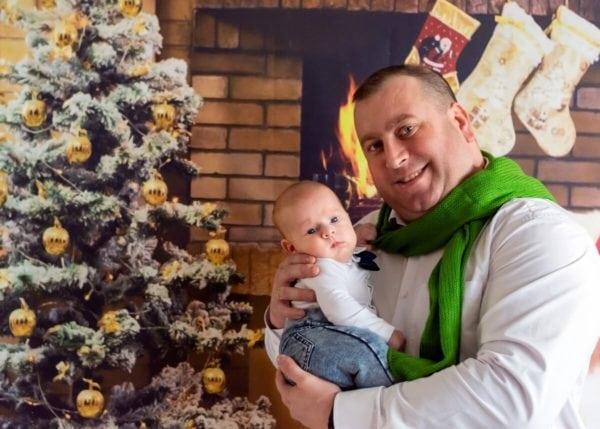 rodzinna sesja świąteczna łódź sesja zdjęciowa w domu sesja niemowlęca niemowlę na rękach taty na tle choinki sz02