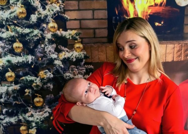 rodzinna sesja świąteczna łódź sesja zdjęciowa w domu sesja niemowlęca mama patrzy ze zdziwieniem na niemowlę