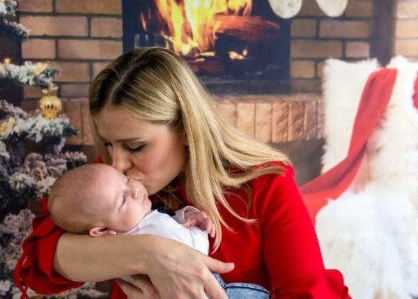 rodzinna sesja swiateczna lodz sesja w domu mama całująca synka na tle kominka sz15