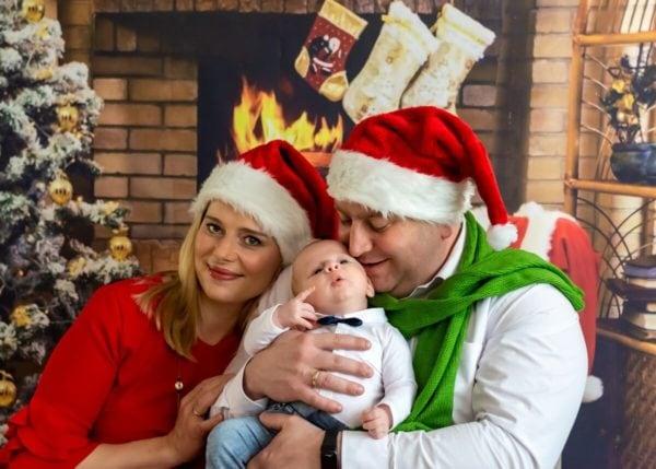 rodzinna sesja świąteczna łódź sesja zdjęciowa w domu przytuleni rodzice w czapkach Mikołaja z synkiem na rękach sz13