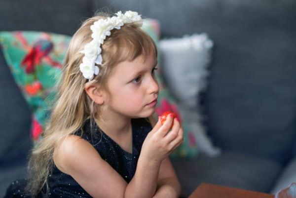 fotograf dzieci łódź sesja dziecięca w domu dziewczynka na sofie zamyślona z truskawką w rączce 06