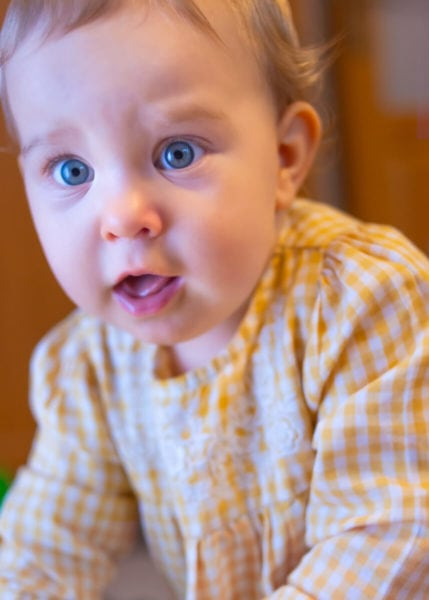 fotograf dziecięcy łódź sesja rodzinna w domu zdziwiona mała dziewczynka z otwartymi ustami i oczami n14