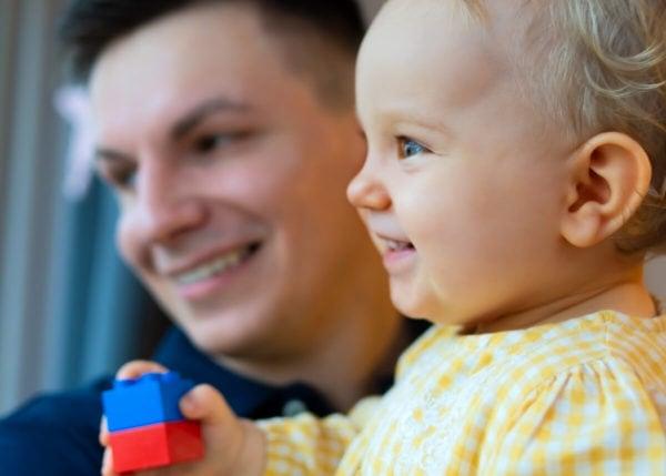 fotograf dziecięcy łódź sesja rodzinna w domu uśmiechnięta mała dziewczynka na rękach taty patrzy w okno n15