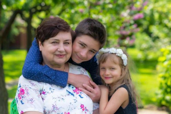 fotografia rodzinna łódź sesja urodzinowa babcia z przytulonymi wnukami w ogrodzie 01