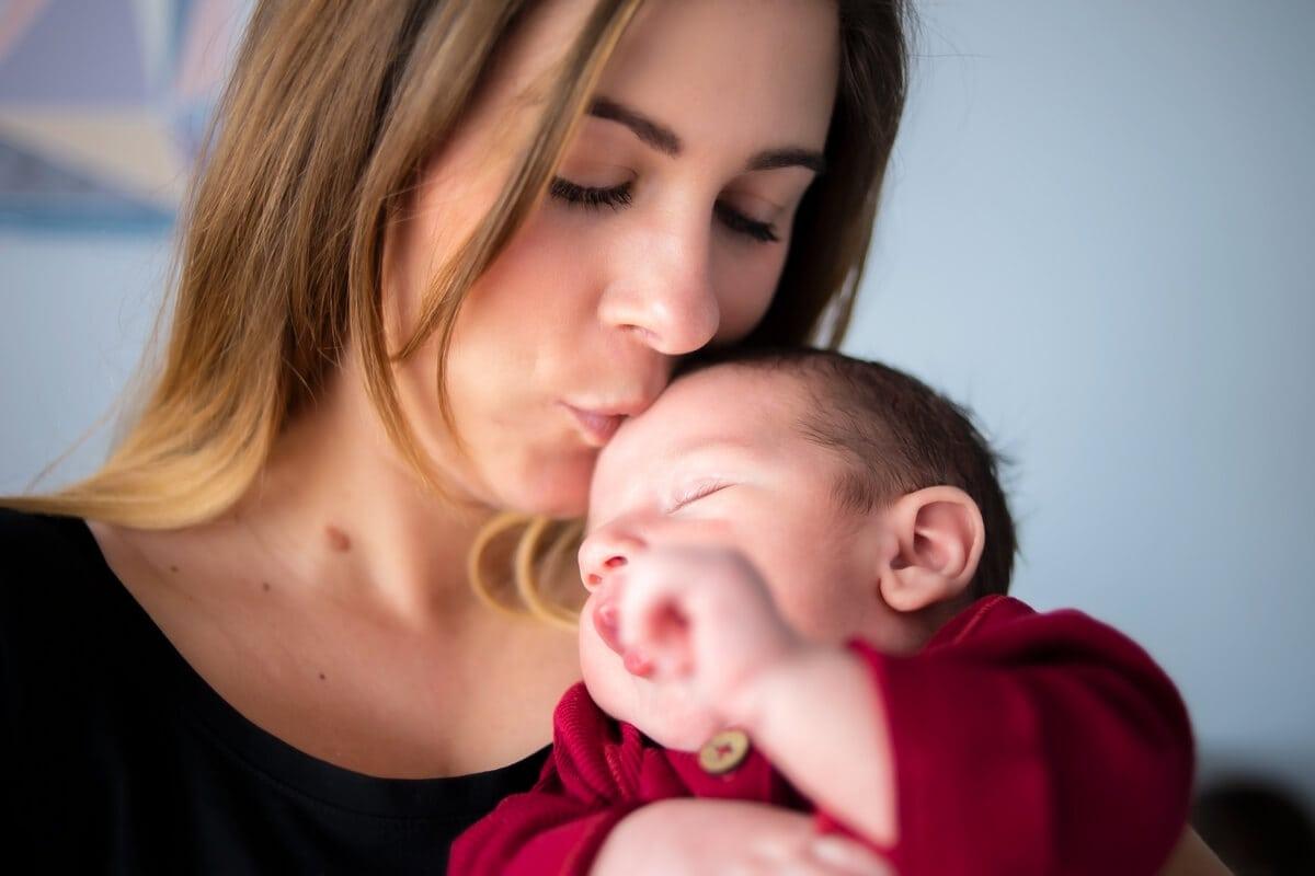 sesja noworodkowa w domu łódź matka całuje w czoło noworodka k03