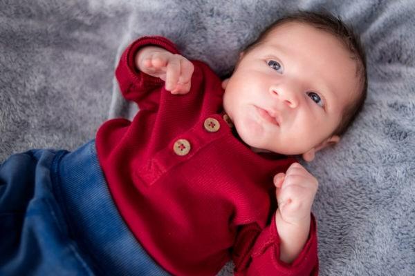 sesja noworodkowa w domu łódź noworodek noworodek leży na plecach i patrzy się w góre K06