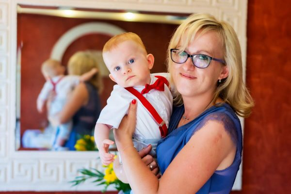 Fotografia chrztu Łódź mama chrzestna z dzieckiem na tle lustra reportaż z przyjęcia