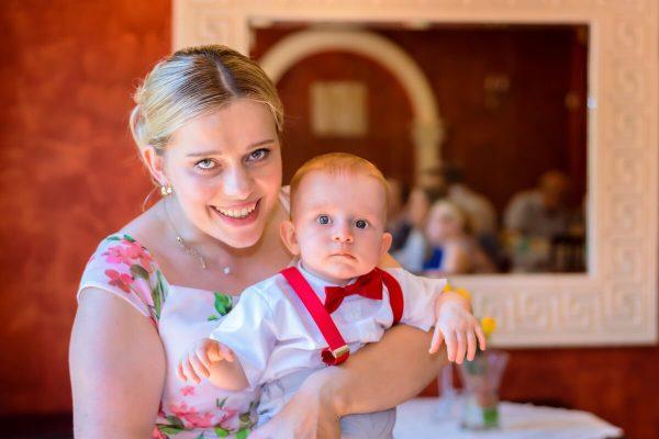 Fotografia chrztu Łódź mama z dzieckiem na tle ściany z lustrem reportaż z przyjęcia