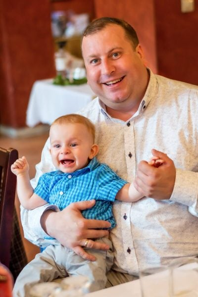 Fotografia chrztu reportaż Łódź tata z synem przy stole oboje rasośni