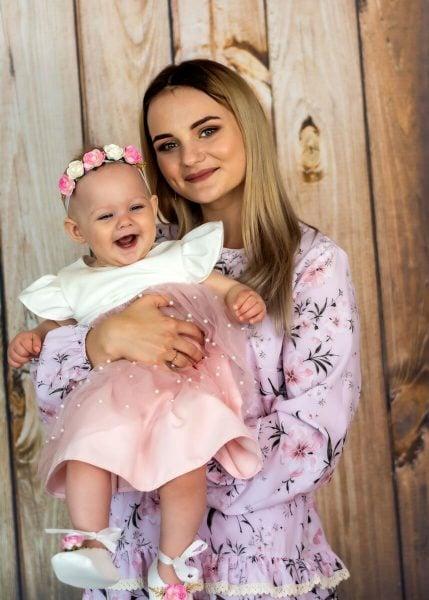 Zdjęcia z chrztu Łódź mama z córką na tle drewnianej ściany