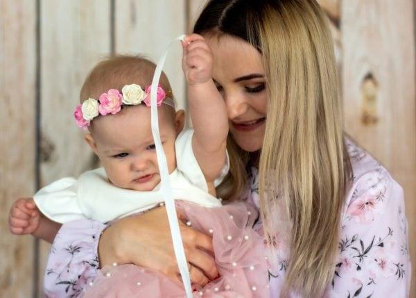 Zdjęcia z chrztu Łódź dziewczynka na rękach mamy bawi się tasiemką