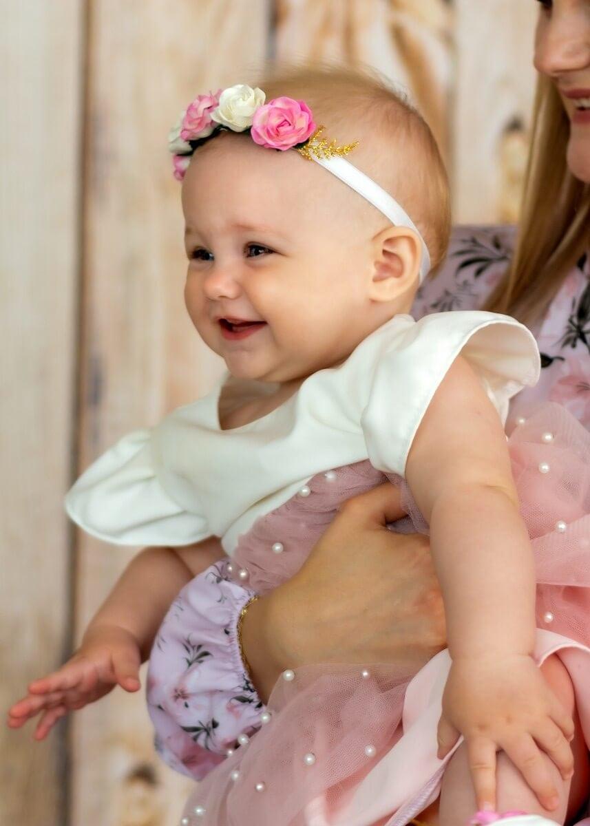 Zdjęcia z chrztu Łódź uśmiechnięta dziewczynka na ręku mamyy L 32