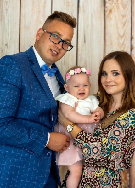 Zdjęcia z chrztu Łódź rodzice chrzestni z dziewczynką na tle drewnianych desek