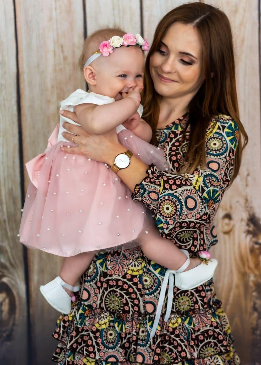 Zdjęcia z chrztu Łódź uśmiechnięta dziewczynka na rękach kobiety jakby w biegu