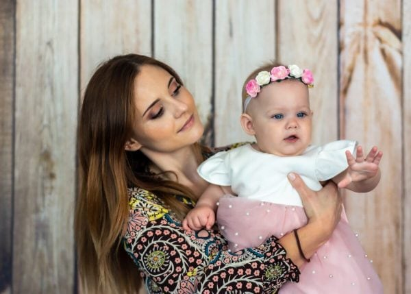 Zdjęcia z chrztu Łódź kobieta trzyma dziewczynkę na ręku, która wskazuje coś rączką