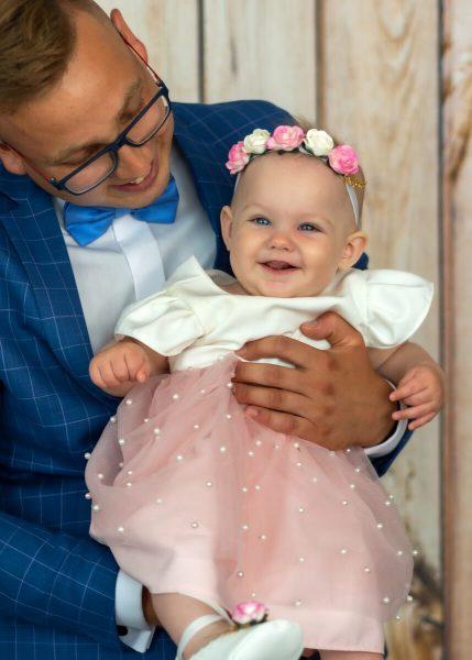 Zdjęcia z chrztu Łódź dziewczynka na rękach mężczyzny, który patrzy na nią z góry i się uśmieca L