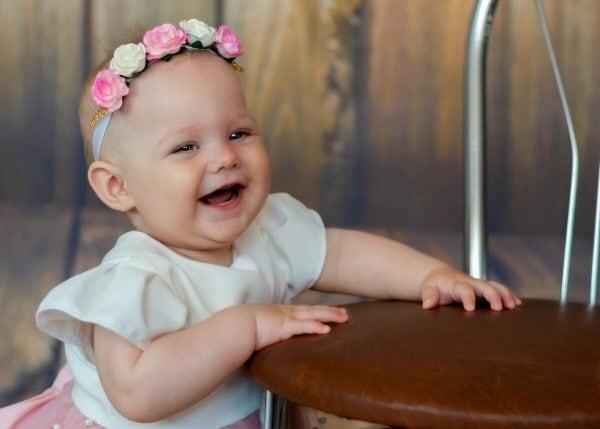 Zdjęcia z chrztu Łódź dziewczynka stoi przy krześle i szeroko się uśmiecha
