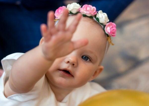 Zdjęcia z chrztu Łódź dziewczynka wyciąga rękę przed siebie by coś sięgnąć L46