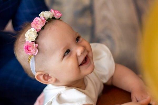 Zdjęcia z chrztu Łódź dziewczynka szeroko się uśmiecha i patrzy do góry