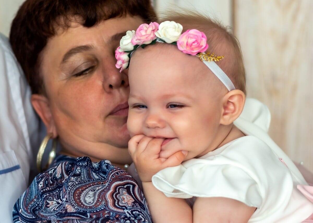 Zdjęcia z chrztu Łódź radosna dziewczynka z wiankiem na głowie przytulona do babci L63