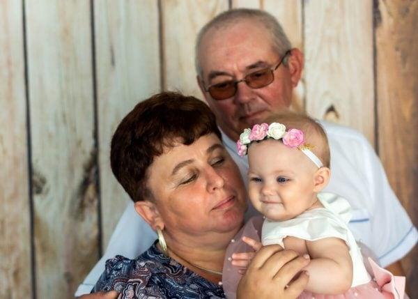 Zdjęcia z chrztu Łódź dziadkowie z wnuczką na tle drewnianych desek L64